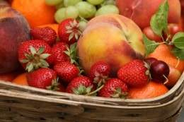 Basket of fruit in season: peaches, strawberries and grapes